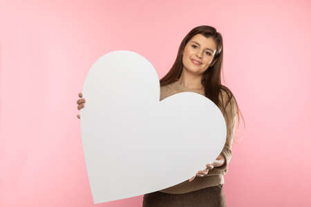 A beautiful girl in love holds a heart shape in her hand. Young woman wants to give a beautiful heart shape as a symbol of love on Valentines Day.