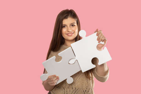 A young adult fits two puzzles together to put them together. Putting together large puzzles by a cute student.