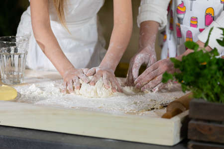Close-up frame. Both girls, mother and five-year-old daughter, knead the cake with their hands on one table, which will be used as a pizza base. The joy of mom and daughter's moments together while working in the kitchen.