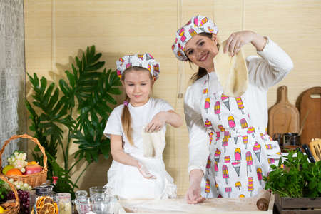 To the top, mother and daughter lifted their rolled cakes onto a flat cake to check that the dough was firm enough. The joy of mom and daughters moments together while working in the kitchen. Banco de Imagens