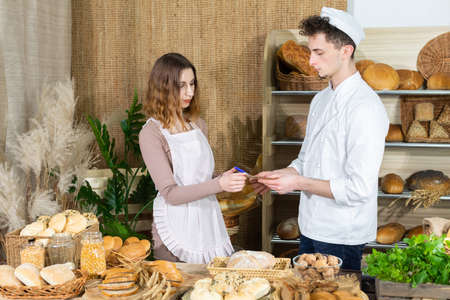 The baker teaches you how to correctly describe prices on wooden plates so that every bread is not accidentally missed. A young saleswoman learns to describe bread. 版權商用圖片