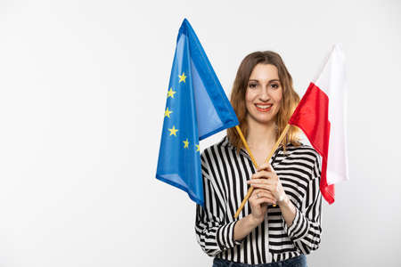 A smiling girl holds two flags in her hand, one is the national flag of Poland and the flag is the European Union. Isolated from the background.