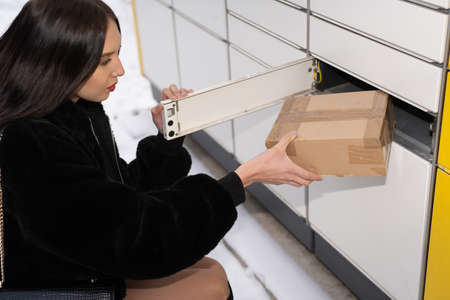 A young adult collects a package from a parcel locker in winter. Automatic machine for sending and receiving letters and parcels.