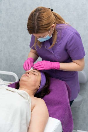 After washing the face with the gel, the beautician wipes dry the remains of the wet gel from the clients face.