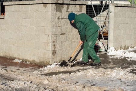 The landlord of the district in a housing estate in the city scrapes the snow off the pavement with a metal shovel