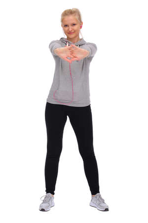 While exercising, the girl stands straddling and stretches out both hands in front of her. Front view