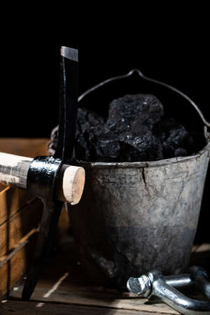 Large pickaxe with wooden handle on black background with lumps of black coal