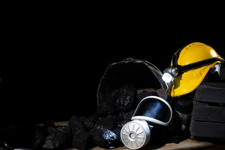On black coal folded mining accessories: yellow helmet with flashlight, dust mask with filter