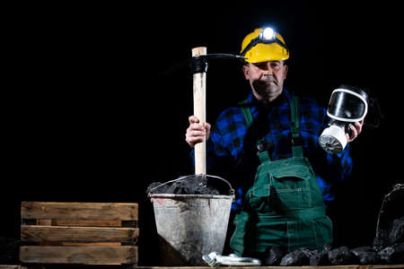 A miner stands holding a pickaxe in one hand and a dust mask in the other, all on a black background