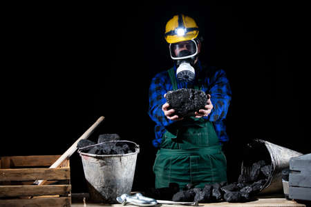 A miner in a helmet with a glowing flashlight and a dust mask on holds a large lump of coal in his hands