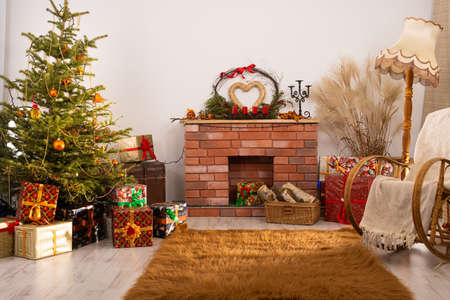 A room with a fireplace decorated for Christmas. Christmas tree with gifts lying under it.