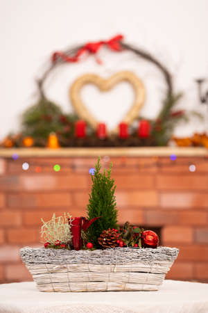 A close-up view of a Christmas reed referring to Christmas. In the background, a fireplace with a large heart-shaped decoration