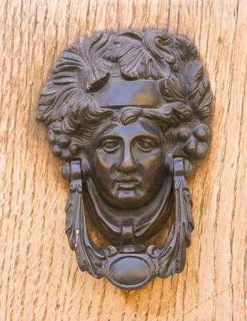 doorknocker: Medieval bronze knocker on the wooden door. Bologna, Italy.