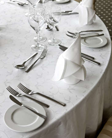 Knife, fork, spoon, plate and glases on a table
