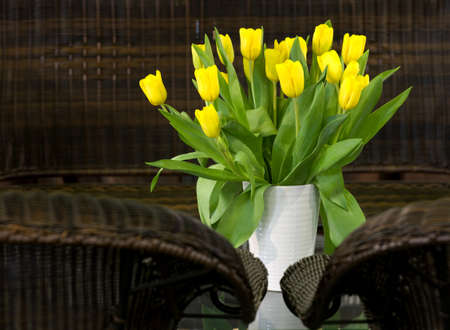 Bouquet of fresh yellow tulips on the glass table