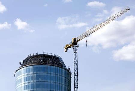 Climber constructor work on blue glass skyscraper  Stock Photo