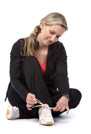 duffel: Young women with sportswear sitt on the floor. White background