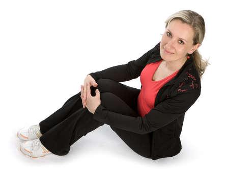 sitt: Young women with sportswear sitt on the floor. White background