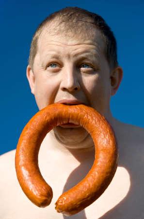 Hungry dicker Mann mit ger�uchertem sasage Lizenzfreie Bilder