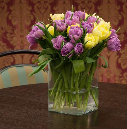 Bouquet von gelben und violetten Tulpen in der Glas-Vase Lizenzfreie Bilder