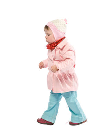 Child walking with pink jacket. Isolated on white