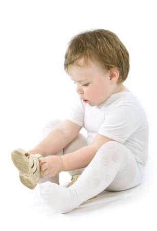 Kinder mit Schuhen Sitzung. Isolated on white