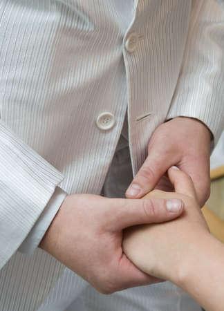 Men and women hends. Men in white wedding suit photo