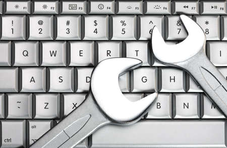 Two metal spanners on the laptop keyboard Stock Photo