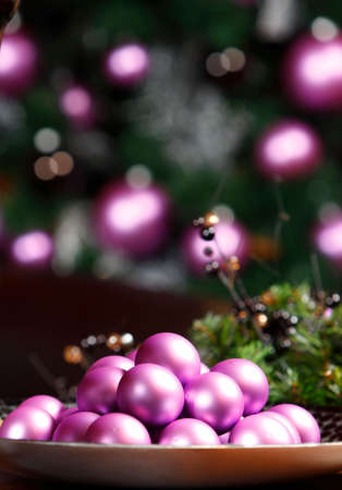 Heap of pink balls, blurred Christmas tree on background photo