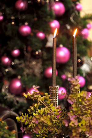 Two candles, pink ball, blured Christmas tree onbackground