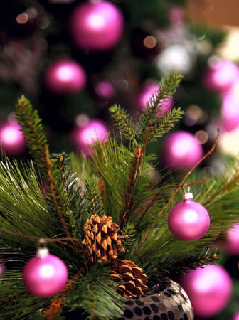 Artificial spruce tree, pink ball, blurred background photo