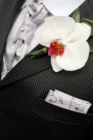 Closeup shot of flower in buttonhole. Groom suit