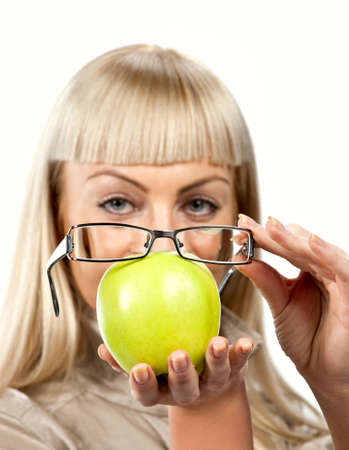 Blonde woman holds green apple with glasses photo
