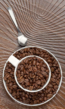 Coffee beans in the cup on brown background Stock Photo