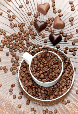 Coffee beans in the cup and chocolate hearts on brown background Stock Photo