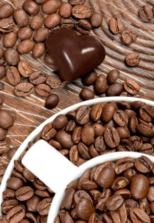 Coffee beans in the cup and chocolate heart on brown background Stock Photo