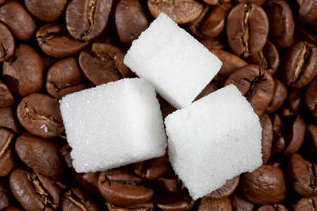 Three pieces of sugar on the roasted coffee beans