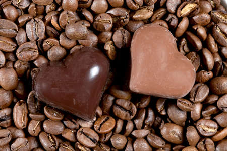 Two chocolate hearts on the roasted coffee beans Stock Photo