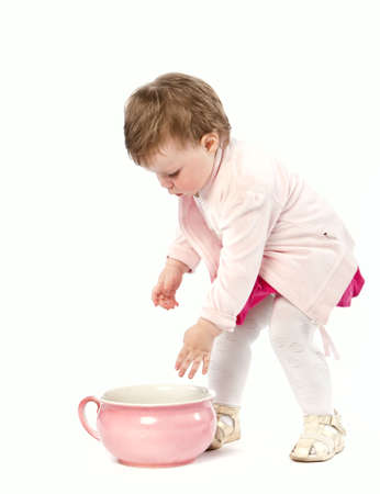 Baby girl with pink potty isolated on white photo