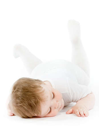 Baby girl in white clothes rest on a white floor photo