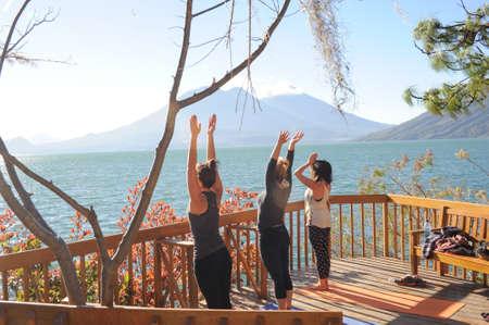 Young girls practicing yoga with view of Lake Atitlan on Guatemala