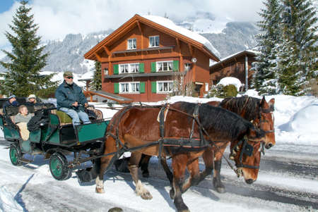 Engelberg, Switzerland - 13 March 2005: Tourists take a ride on a horse-drawn carriage in the snowy streets of Engelberg in the Swiss Alps