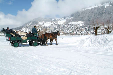 brougham: Engelberg, Switzerland - 13 March 2005: Tourists take a ride on a horse-drawn carriage in the snowy streets of Engelberg in the Swiss Alps Editorial