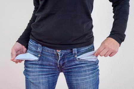 お金がなければ空のポケットを示す女性