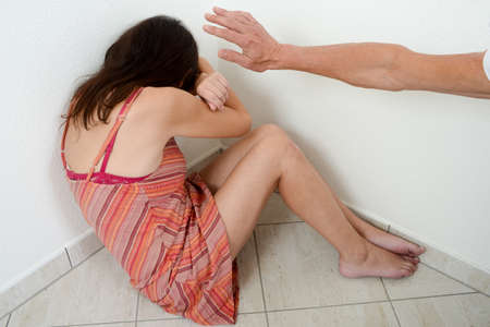 Domestic violence against a woman in a corner