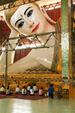 buddhism prayer belief: Yangon, Myanmar - 1 April 2010: belivers praying at the pagoda Chaukhtatgy of Yangon on Myanmar