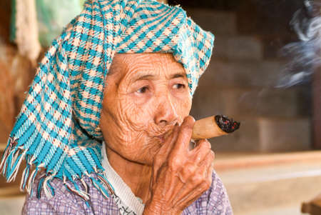 cheroot: Minnanthu, Myanmar - 24 January 2010: Portrait of an old woman smoking a big cigar at the archaeological site of Bagan on Myanmar