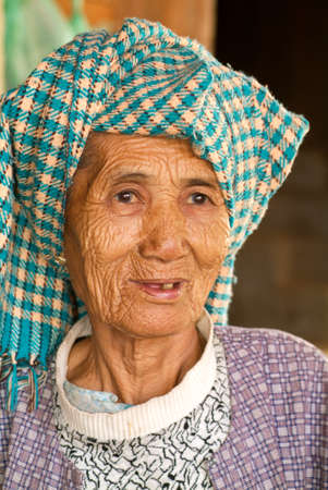 cheroot: Minnanthu, Myanmar - 24 January 2010: Portrait of an old woman at the archaeological site of Bagan on Myanmar