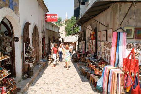 gouged: Mostar, Bosnia Herzegovina - 2 September 2004: tourists walking between the gift shops at Mostar