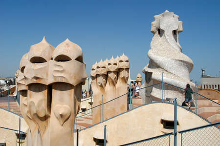 famous building: BARCELONA, SPAIN - 15 July 2004: People walking on the roof of Casa Mila or La Pedrera in Barcelona, ??Spain. This famous building was designed by Antoni Gaudi and is one of the most visited of the city Editorial